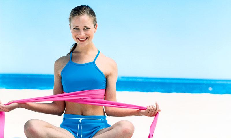 Chica con banda elástica en la playa
