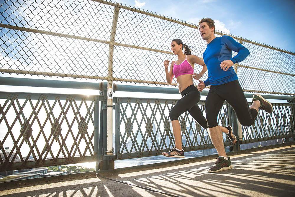 Hombre y mujer corriendo por la ciudad